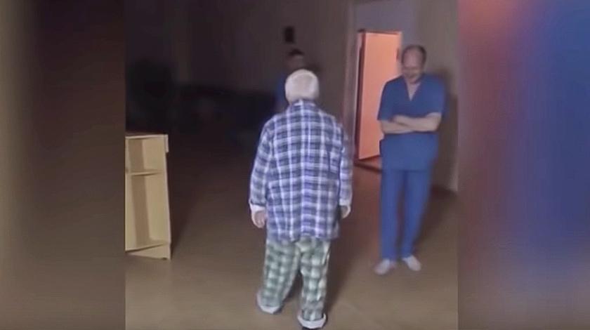 В ролике видно, как один иРсотрудников лечебного учреждения бросает в мужчину тапок, а потом пинает его под Ðад